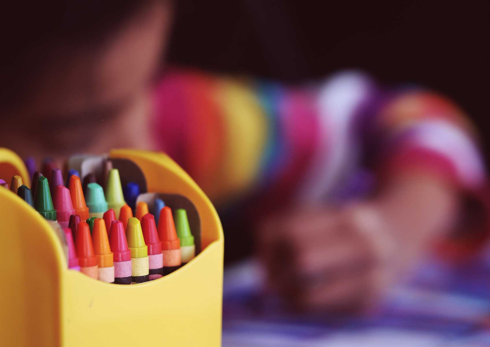 A box of crayons in front of a child who is coloring