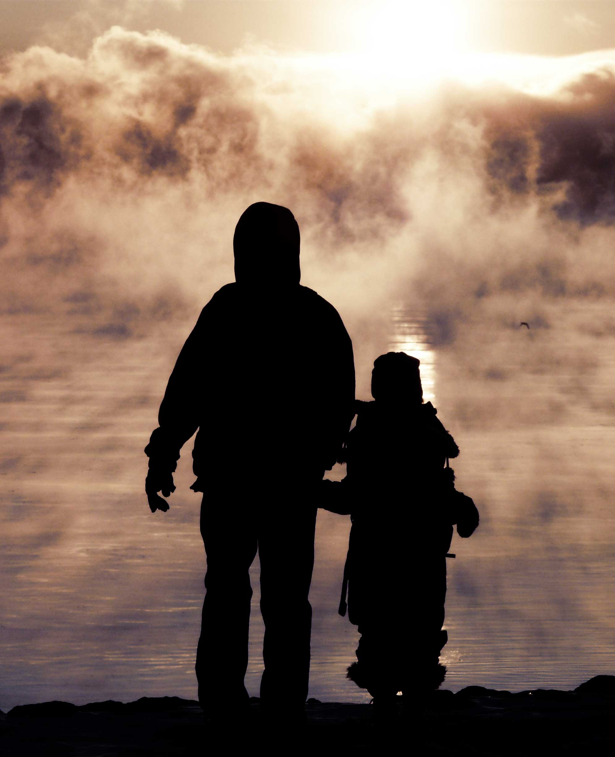 A father holds hands with his daughter as they walk towards the sunset