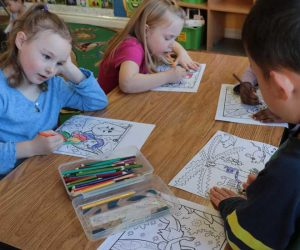 Young children coloring together on a table