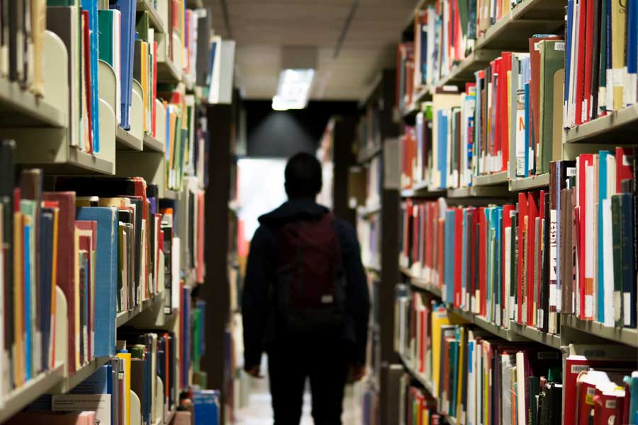 A high school student walking through a library