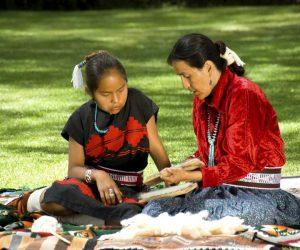 An Aboriginal Elder instructing a young child